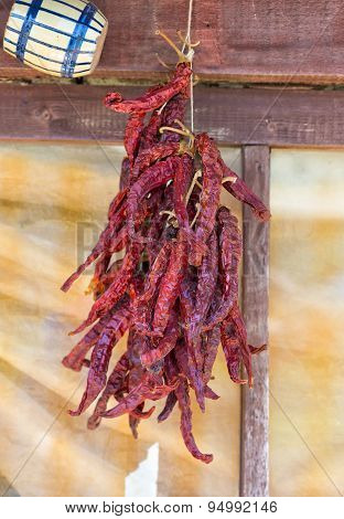 Bunch Of Dried Red Chilli Peppers On A Wooden Board