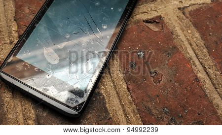 Cell phone with broken screen close up on brick background