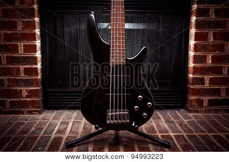 Five string bass guitar in front of fireplace