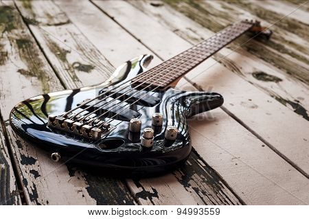 Black bass guitar on a wooden background