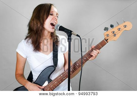 Girl singing with microphone and bass guitar isolated on gray background