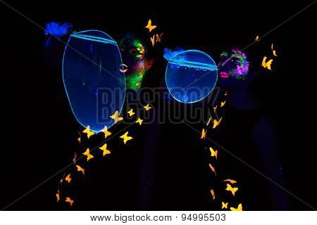 Image of two women with bubbles, luminous make up