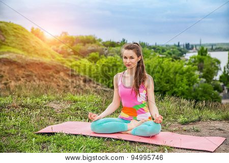 Pretty Woman Doing Yoga Exercises On Nature Landscape