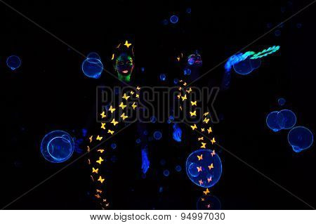 Image of two women blowing luminous bubbles