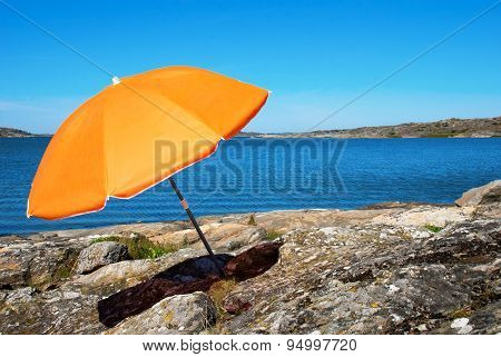 Swedish Coast With Blue Sea And Orange Parasol