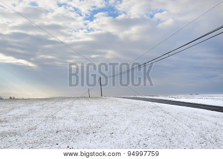 Snowy Landscape with Lonely Road and Dramatic Sky