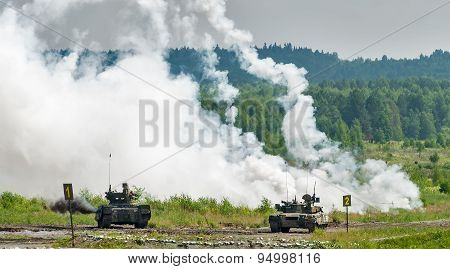 Military tanks hide behind smoke screen