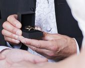 picture of altar  - Best man presenting gold wedding rings to bride and groom at the altar - JPG