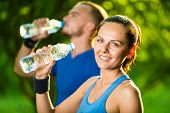 Man and woman drinking water from bottle after fitness sport exercise poster