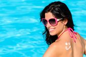image of sunbather  - Happy woman with sunscreen lotion funny smiley on her back enjoying summer vacation at swimming pool - JPG