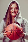 pic of hoods  - Happy sporty teenager girl wearing hooded sweatshirt holding basketball. Teen sport. ** Note: Soft Focus at 100%, best at smaller sizes - JPG