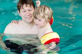 stock photo of floaties  - Young man teaching his little active son to swim in an indoor swimming pool - JPG