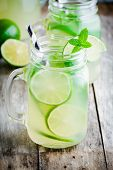 foto of mason  - homemade lemonade with lime mint in a mason jar on a wooden rustic table - JPG