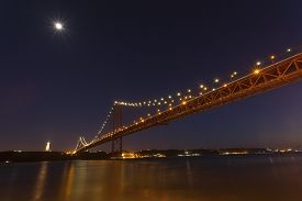 stock photo of bridge  - The 25th April bridge in Lisbon at night under a full moon - JPG