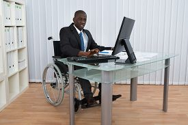 pic of wheelchair  - Portrait Of Happy African Businessman Working In Office Sitting On Wheelchair - JPG