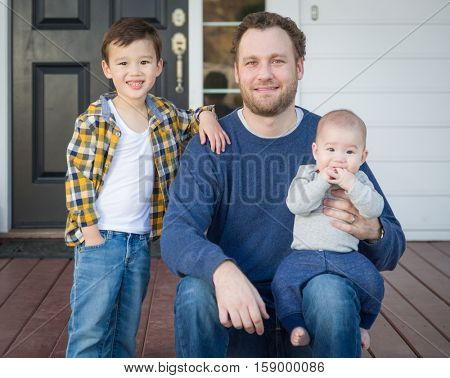 Young Mixed Race Father and Sons on Front Porch.