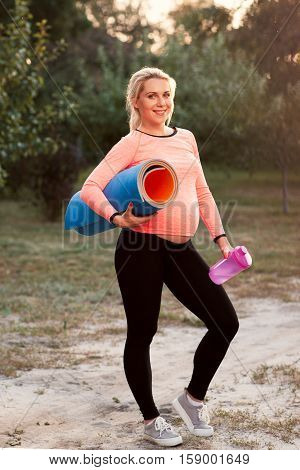 Smiling pregnant woman ready for fitness outdoor. lady posing with mat and bottle of water. Health and body care, sport, pregnancy concept