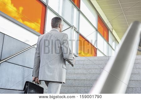 Rear view of middle aged businessman walking up stairs in railroad station
