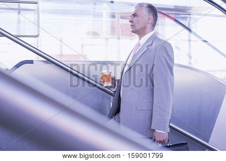 Side view of middle aged businessman with coffee cup walking up stairs in railroad station