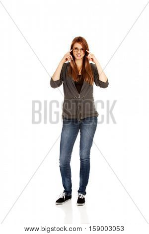 Pretty teenage woman improving glasses.
