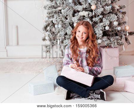 Beautiful blonde girl 12-15 year old sitting with Christmas presents under Christmas tree. Sitting on floor in room. Teenagerhood.