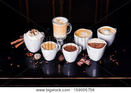 coffee assortment on a dark table with chocolate and cream