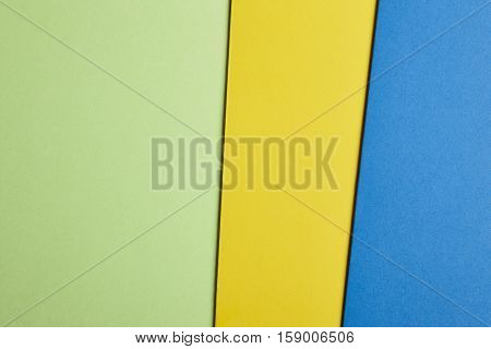 Colored cardboards background in green yellow blue tone. Copy space. Horizontal