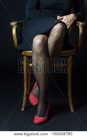 Woman in red pumps and black stockings is sitting on an old chair. Thus crossed legs suggest a slight shyness and also readiness to flirt