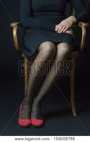 Woman in red pumps and black stockings is sitting with parallel legs on an old chair. This position reflects smartness confidence creditibility.