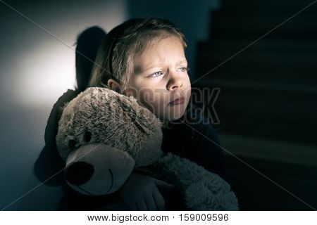 Sad little girl embracing her teddy bear - feels lonely - if you are small girl teddy bear is willing to be your best friend