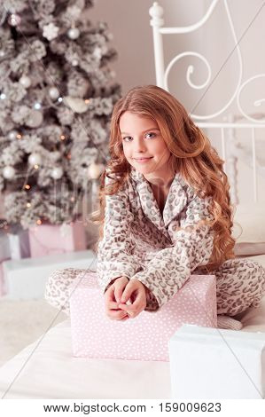 Smiling teenage girl siting in bed over Christmas tree in room. Wearing pajamas. Looking at camera. Open presents. Holiday time. Christmas morning.