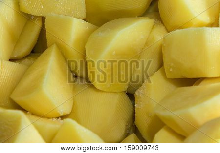 Pieces of sliced yellow raw potatoes with salt