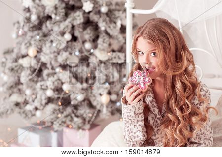 Beautiful blonde girl 12-14 year old eating gingerbread at Christmas morning. Bed time. Childhood.