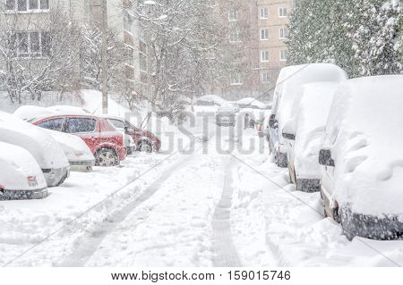 Snowstorm snow-covered street and cars with a lonely pedestrian