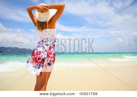 Young woman in summer dress standing on sand and holding straw hat looking to a sky