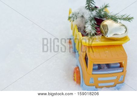 A toy truck delivering a heart shaped toy overhead shot holidays background