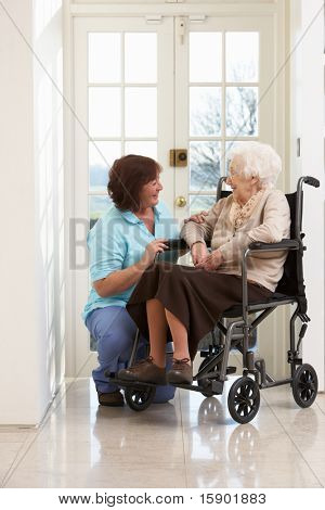 Carer With Disabled Senior Woman Sitting In Wheelchair