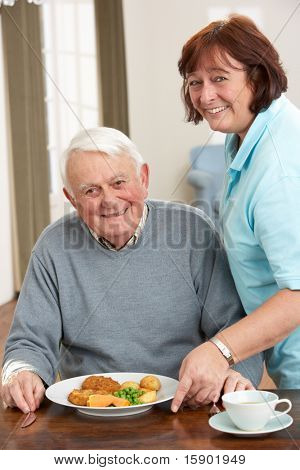 Senior Man Being Served Meal By Carer