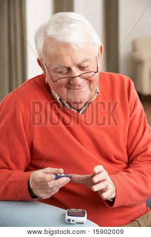 Senior Man Checking Blood Sugar Level At Home