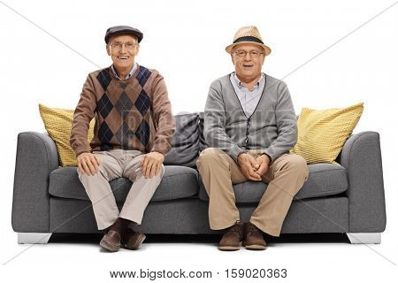 Two joyful elderly men sitting on a sofa isolated on white background