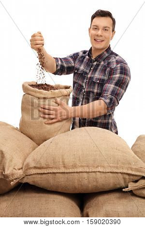 Young farmer filling a burlap sack with coffee beans isolated on white background