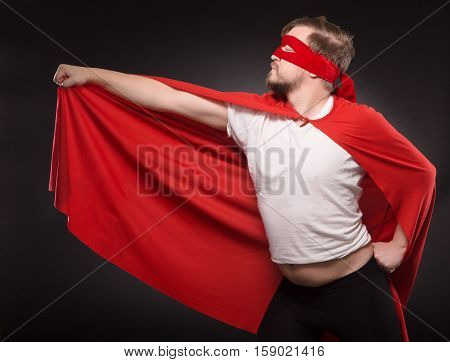 Handsome young super hero man posing in studio. Funny man in red mask showing his red coat while posing for photographer isolated on black background.