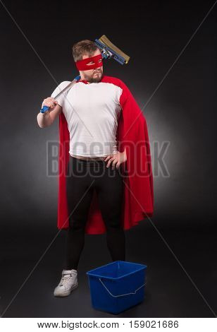 Cleaning concept. Handsome super hero man with red mask on posing for photographer with cleaning equipment. Superhero concept.