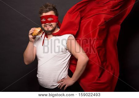 Super hero glutton man eating hanburger isolated on black. Handsome man with red mask on posing for photographer. Super hero concept.