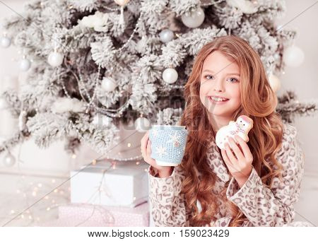 Cheerful teenager girl 12-15 year old holding cup of tea and gingerbread over Christmas tree. Posing in room. Looking at camera. Laughing kid.