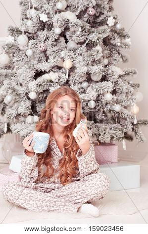 Smiling teen girl 10-15 year old sitting under Christmas tree drinking tea eating cookie in room. Looking at camera. Childhood.
