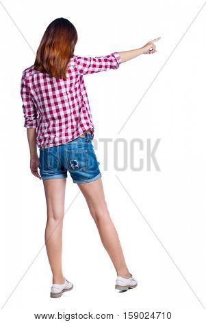 Back view of  pointing woman. beautiful girl. Rear view people collection.  backside view of person.  Isolated over white background. Girl in shorts and checkered shirt shows a finger in the side.