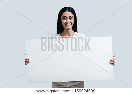 Beautiful and full of energy. Young confident woman holding blank flipchart and looking at camera while standing against grey background