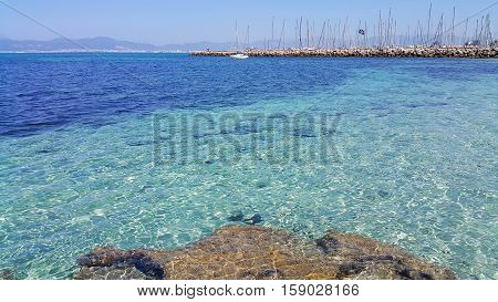 Beautiful sea views with transparent turquoise water yachts and Palma de Mallorca on the horizon. L'Arenal Majorca Balearic Islands Spain.
