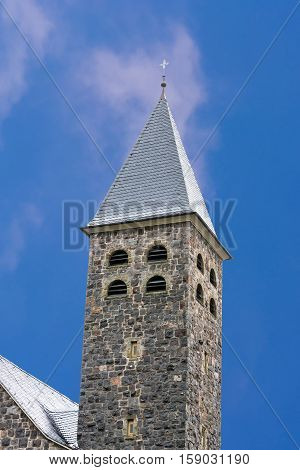 Tower spire of a church in Antfeld in Sauerland Germany against blue sky.